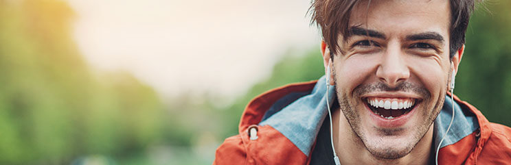 Man with orange and blue jacket wearing earbuds, smiling outside